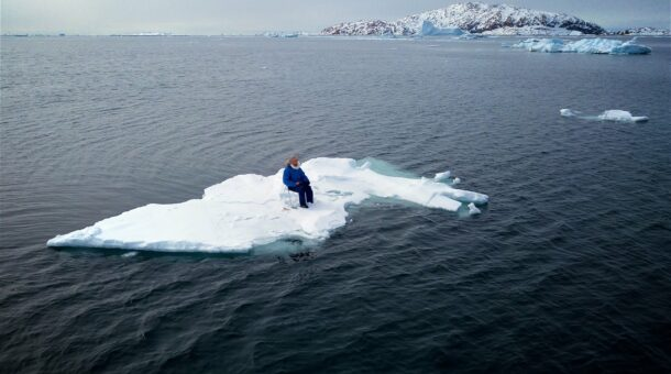man sitting on iceberg floating out to sea