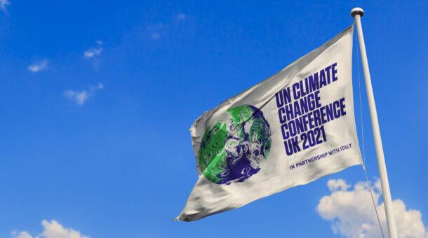 COP26 flag blowing in the wind against blue skies